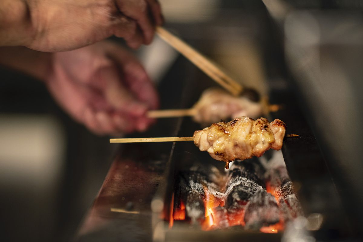 Pieces of chicken are held up by chopsticks and grilled over an open flame with charcoal.
