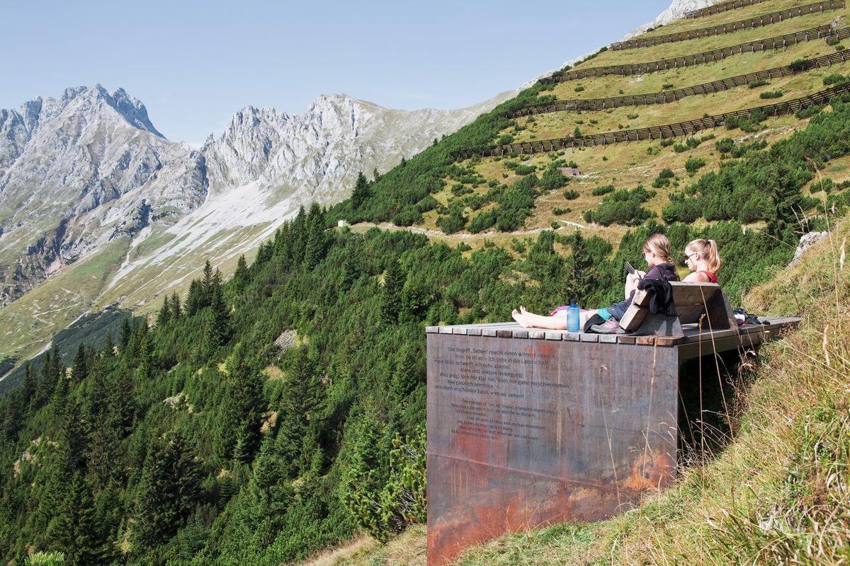 People sitting on metal box in alps