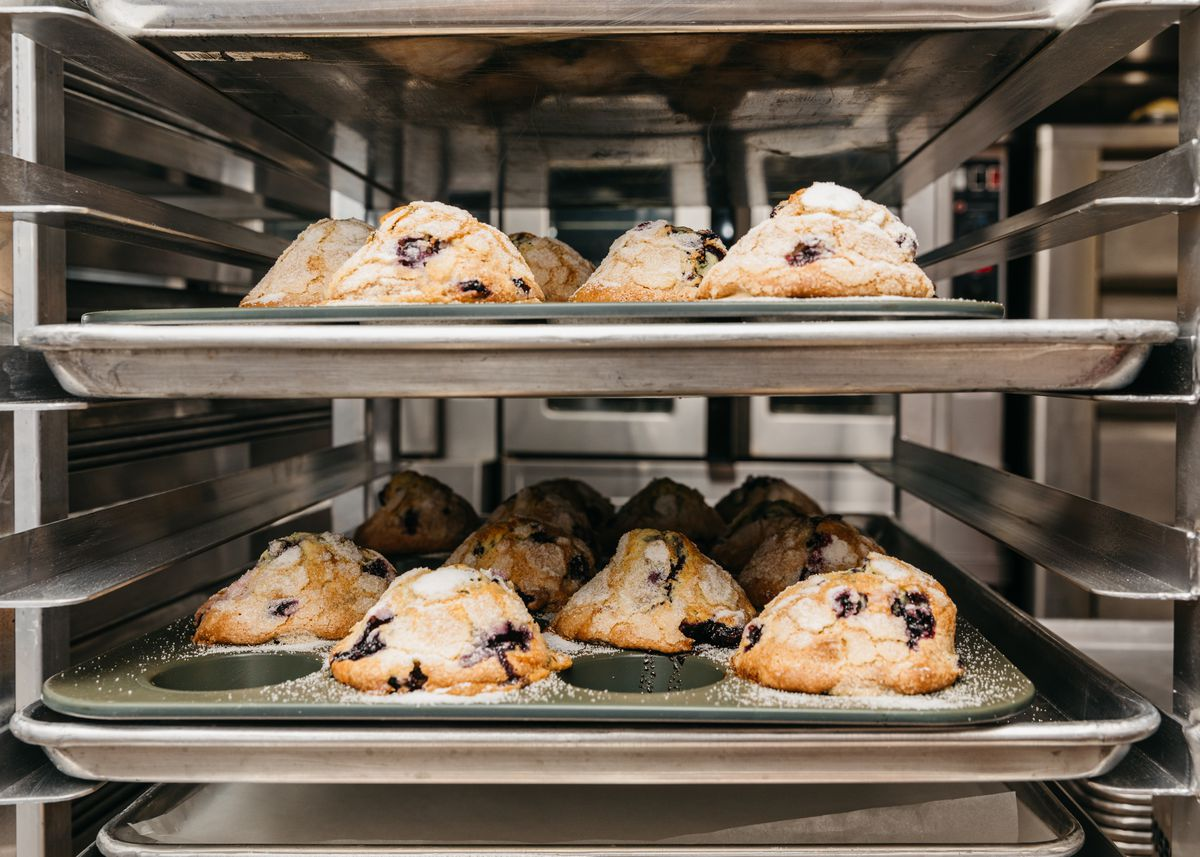 Two metal trays of large, sugar-topped blueberry muffins sit in a speed rack in a professional kitchen.