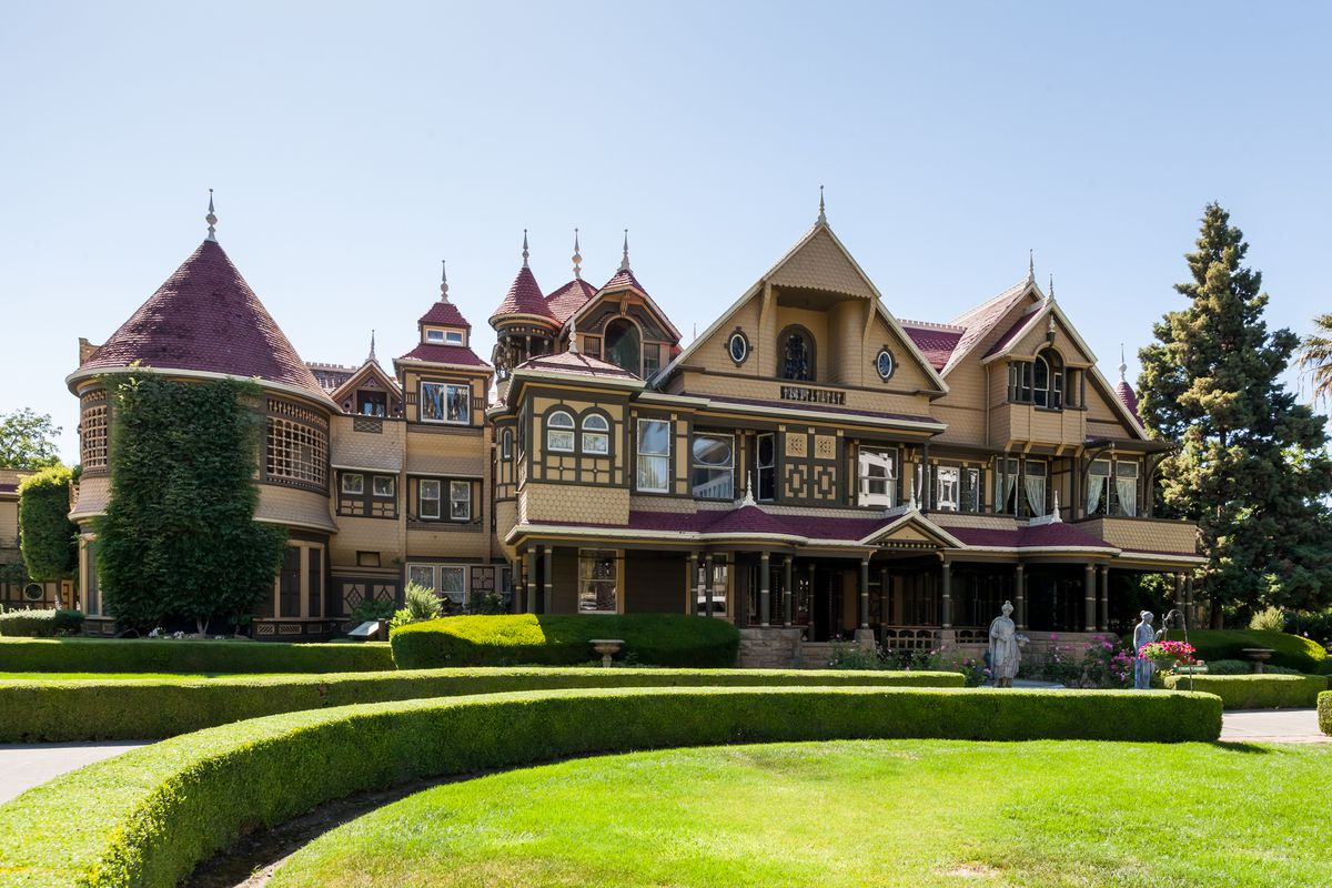 The facade of an old Victorian mansion with a green lawn in front.