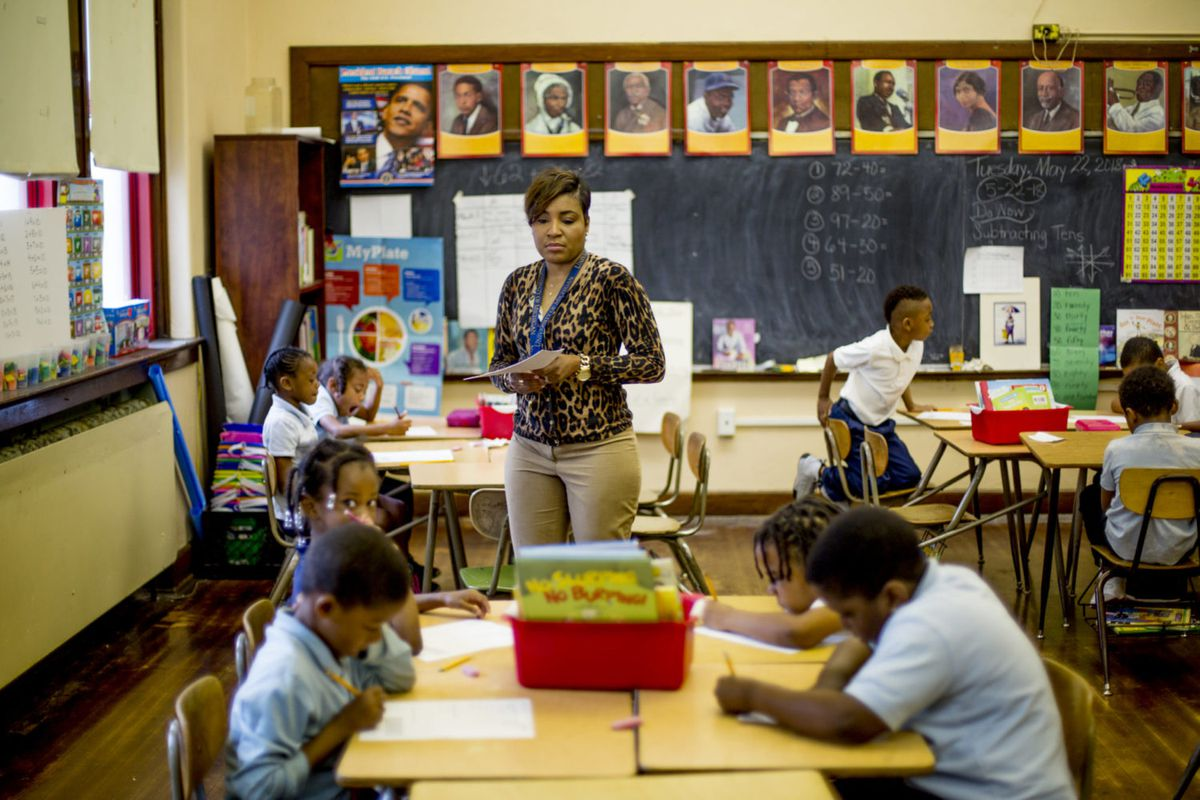Rynell Sturkey teaches first-grade at Detroit's Paul Robeson Malcolm X Academy. Several students work at desks around her.