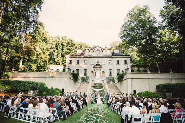 In the distance is a large white house. In the foreground are many rows of chairs with people sitting on them. There is a path leading to the house. There is a bride and groom at the end of the path in front of the house.