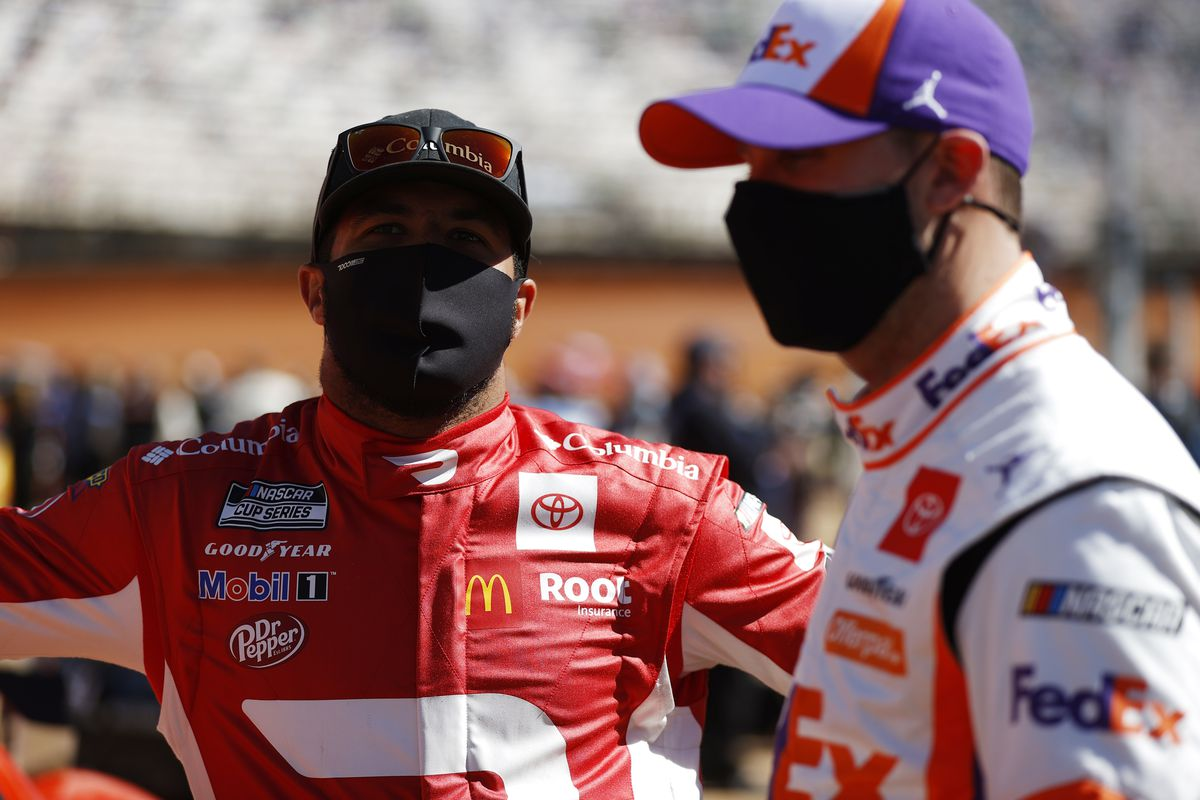 Denny Hamlin, driver of the #11 FedEx Freight Toyota, talks with Bubba Wallace, driver of the #23 DoorDash Toyota, during the NASCAR Cup Series Food City Dirt Race at Bristol Motor Speedway on March 29, 2021 in Bristol, Tennessee.