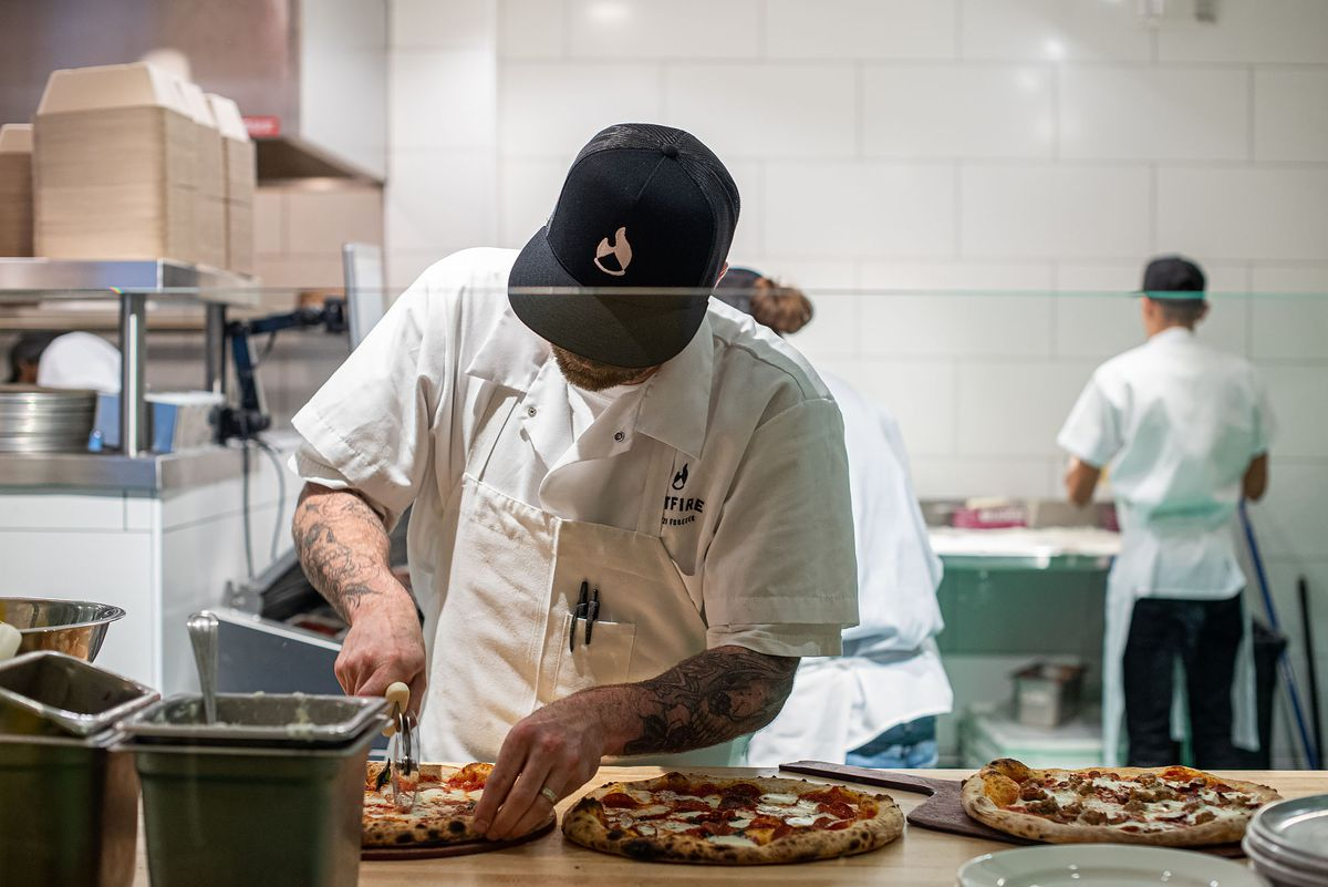 A pizza maker cuts finished pizzas by hand.