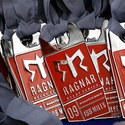 Medals wait at the finish area of the Ragnar Relay Wasatch Back in Park City on Saturday after teams completed the 188-mile journey. At right, Kris Porter, of Salt Lake City, finishes the Ragner Relay Wasatch Back.
