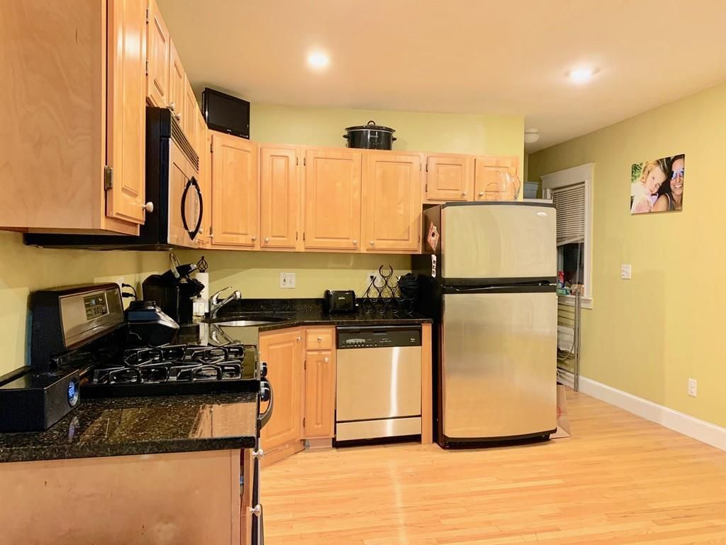 A kitchen with an L-shaped counter and the fridge at one end of it.