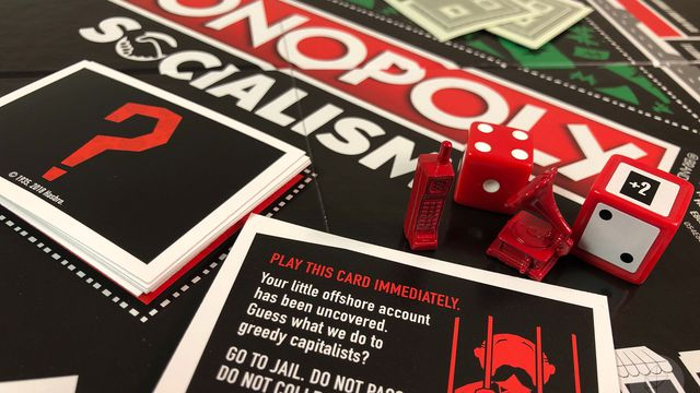 "An image of the all-black paper components of Monopoly Socialism: Winning is for Capitalists. The Chance card on display shows a man in jail and says ""Guess what we do to greedy capitalists?"""