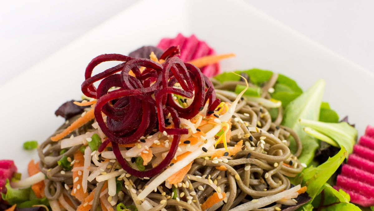 Noodles sit atop a bed of lettuce, and are topped with spiralized beets, sprouts, and various seeds.