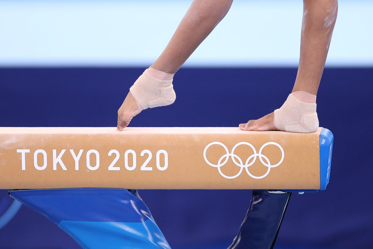 "A gymnast's feet balance on a balance beam, which reads ""TOKYO 2020."""