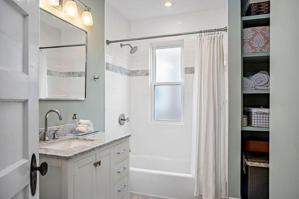 A small bathroom with the curtain pulled back on the shower.