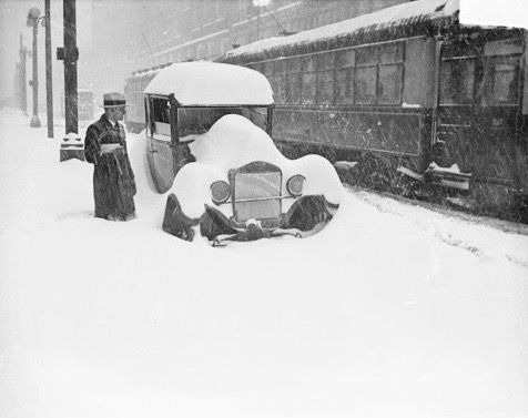 Image of a man standing in knee deep snow next to an automobile with snow piled on the roof, hood and around the wheels on a street inChicago,Illinois. A streetcar (trolley car) is moving through the snow past the automobile on the right.