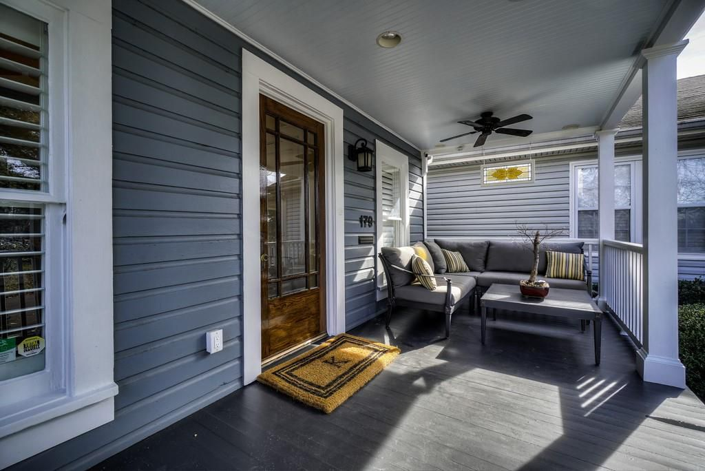 A front porch with ceiling fans and a lot of seating.