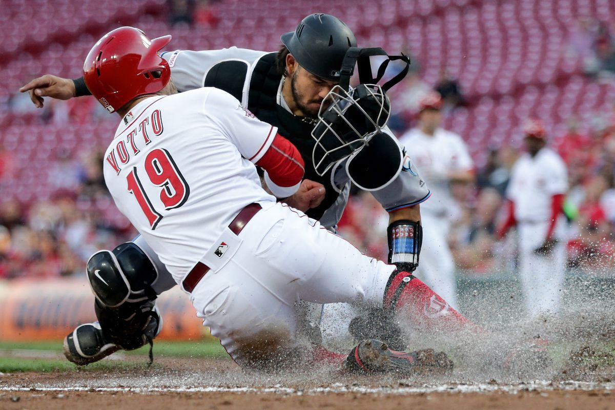 Cincinnati Reds first baseman Joey Votto (19) is tagged out at the home plate by Miami Marlins catcher Jorge Alfaro (38) in the first inning of an MLB baseball game, Wednesday, April 10, 2019, at Great American Ball Park in Cincinnati.