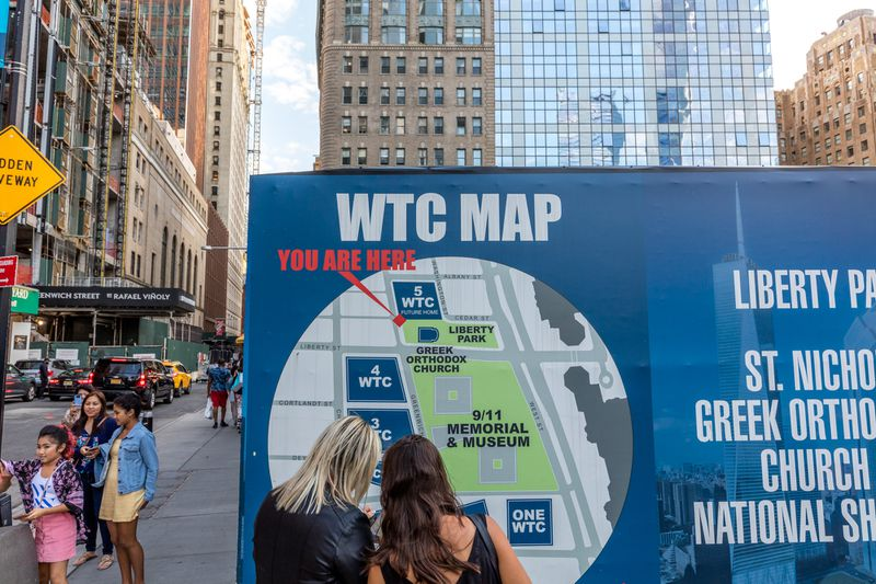 "Two women stand in front of a map showing buildings on a large urban campus. The text on the map reads ""WTC MAP."""