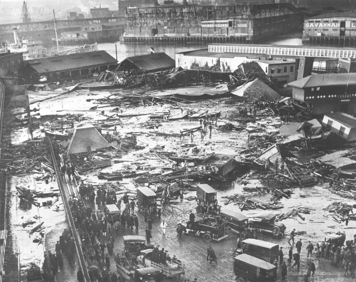A decimated urban landscape, with ruined buildings and people standing about.