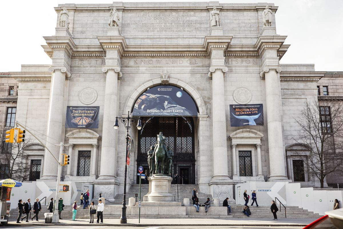 The exterior of the American Museum of Natural History. The facade is white with columns.
