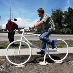 Mel Crow pretends to ride a ghost bike while his brother Allen takes a photo at a memorial in honor of their father, Douglas Crow, in Provo, Wednesday, May 20, 2015. At center back is another brother, Jeremy Crow.