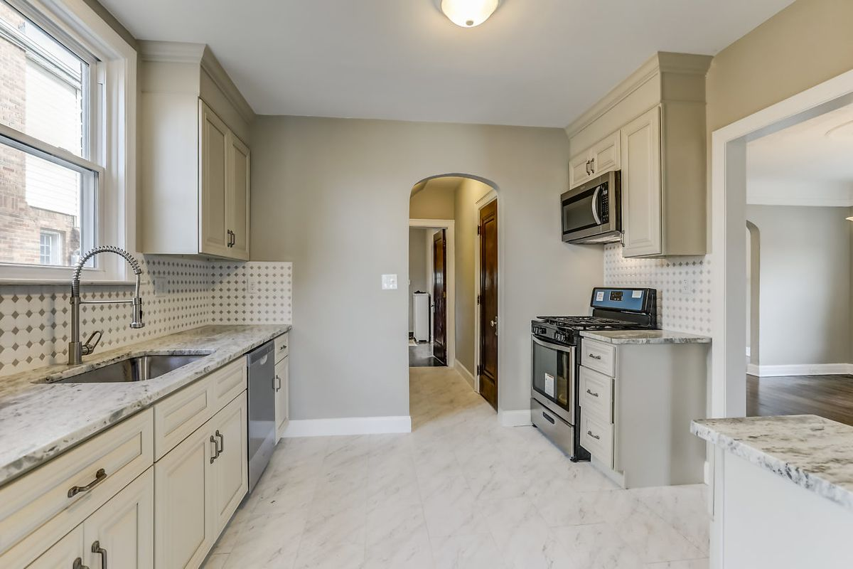 A kitchen with white granite countertops and white cabinets.