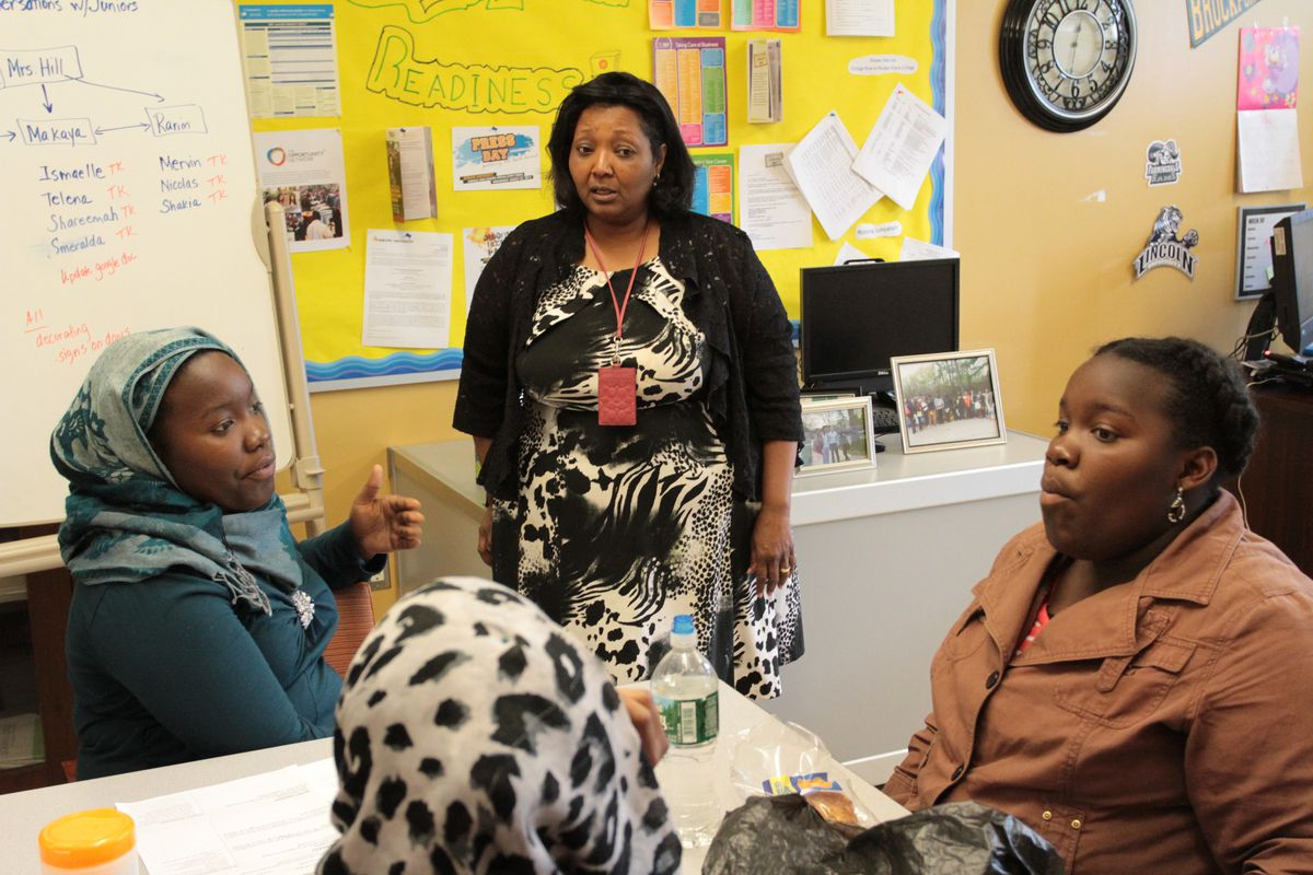 Michele Hill, college and career program director at Brooklyn Generation School, speaks with Ismaelle Oriental, 15, (left) and her twin sister, Elodie.