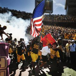 Minnesota's Ra'Shede Hageman (99) carries the United States flag as the teamtakes the field to play New Hampshire in an NCAA college football game, Saturday, Sept. 8, 2012, in Minneapolis. Minnesota won 44-7.