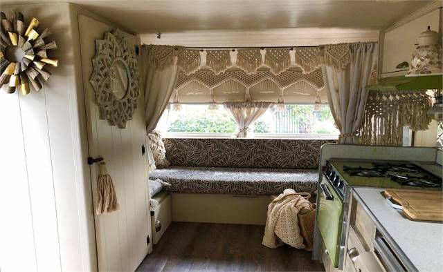 The interior of a camper trailer. There is a kitchenette with a stove, oven, and countertop. There is a patterned seat. Various art hangs on the walls.