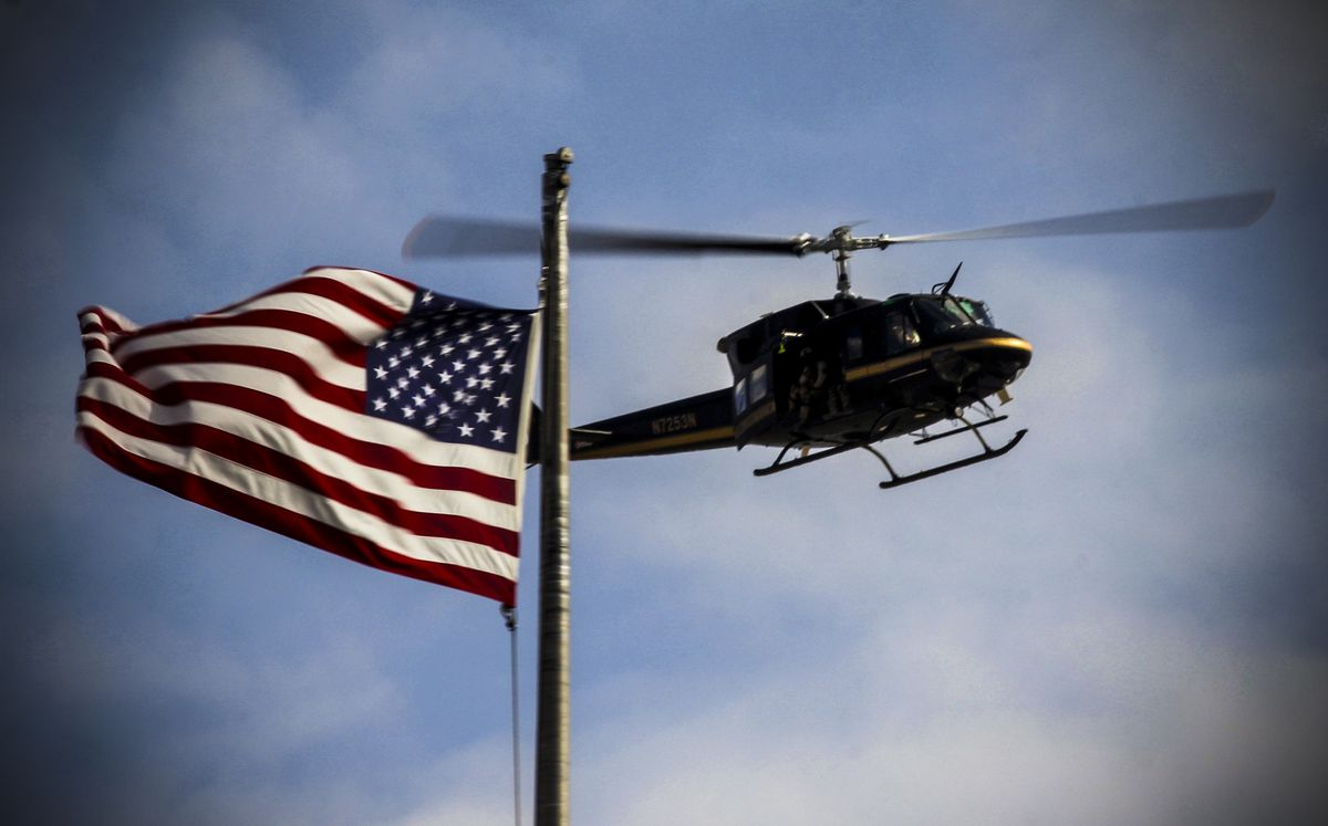 A US customs and border patrol helicopter overflies a US flag in El Paso, Texas at the US-Mexico border, during a crowd control drill, as seen from Ciudad Juarez, Mexico, on November 9, 2018.