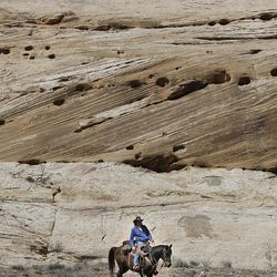 Bobby Lee Thompson is framed by windblown rock as he rides down the Little Grand Canyon of the San Rafael Swell  Saturday, April 2, 2011, in the San Rafael Swell in Central Utah.