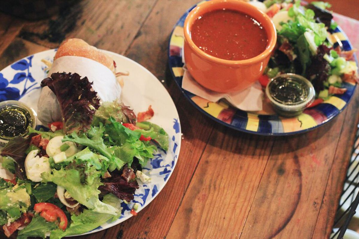 A plate with a green salad and half sandwich and a second plate with a bowl of tomato soup and a salad