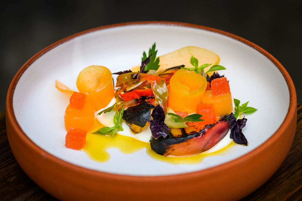 Peach, feta and compressed melon with Jimmy Nardello peppers, ginger and basil in a white and terra cotta bowl