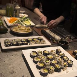 Vegan chef Molly Aubuchon slices vegan maki rolls made with the help of her son Sam, 11, Monday, Feb. 8, 2016, in her Kent, Ohio, home.