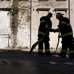 Firefighters pack up equipment in the aftermath of a fire in a warehouse on York Street near Kensington Avenue in Philadelphia on Monday, April 9, 2012. Two firefighters died after a wall collapsed on them while they fought the massive early-morning blaze.