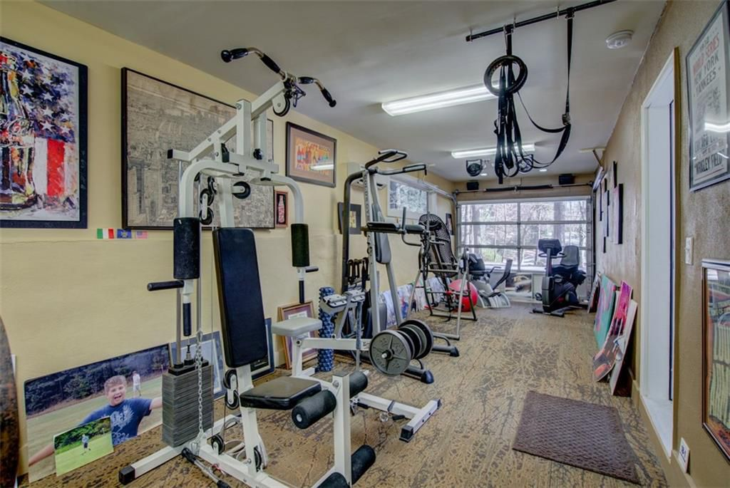 A home gym with a garage door and brownish walls.