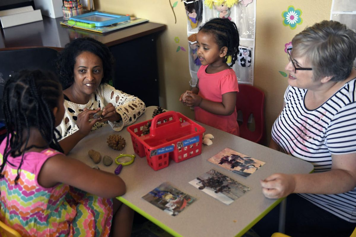 Yemi Habte works with her daughters Charis Mandefro 9, and Anna Mandefro 2, as Stephanie Olson of Aurora, a MyVyllage mentor, watches during a mentoring session in Habte's home.
