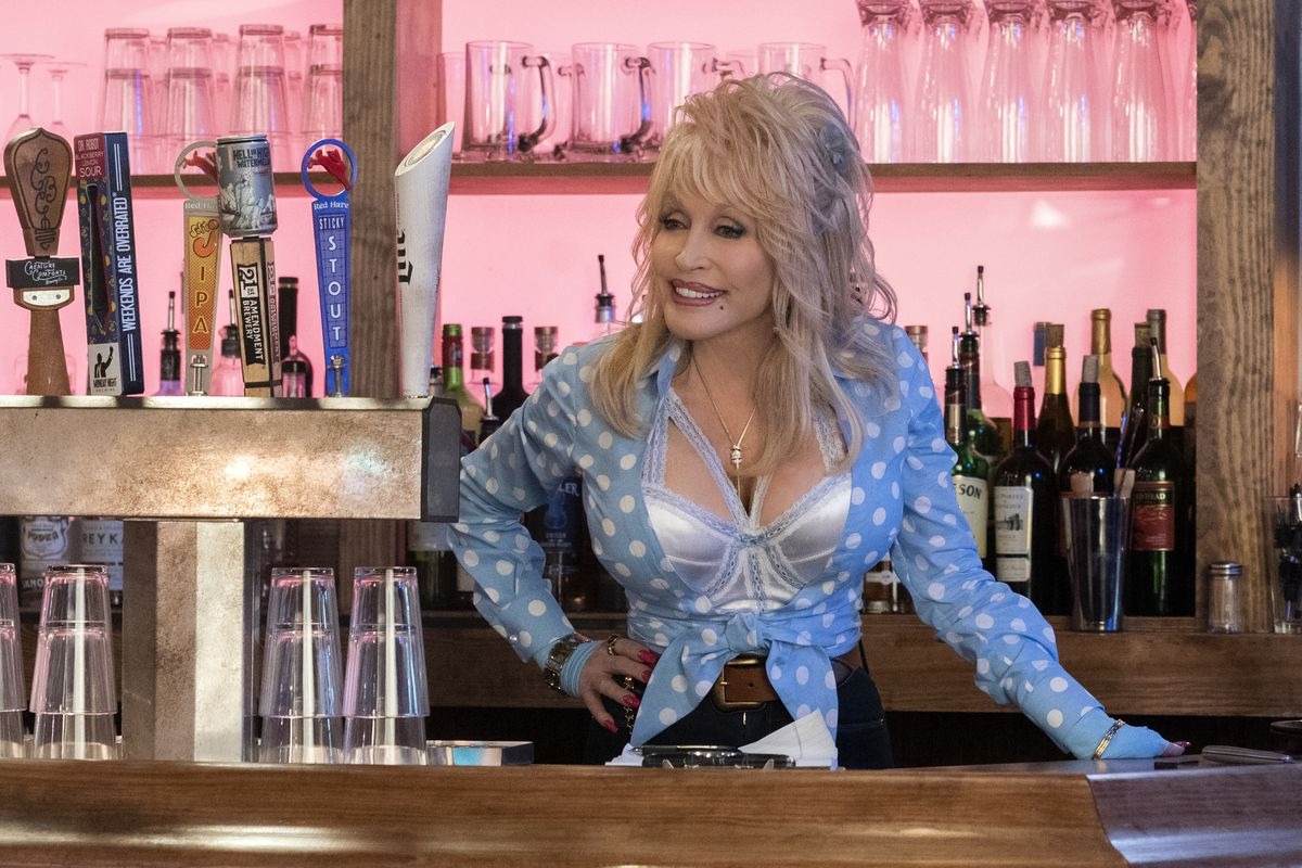 Dolly parton in a fabulous low cut blue shirt, standing behind a bar. Her smile is bright and inviting. Dolly will solve your problems. Dolly is here for you.