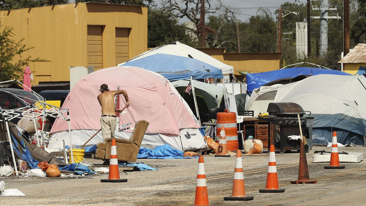 A man works near his tent at Camp Esperanza homeless camp in Austin, Texas, on Tuesday Oct 20, 2020.