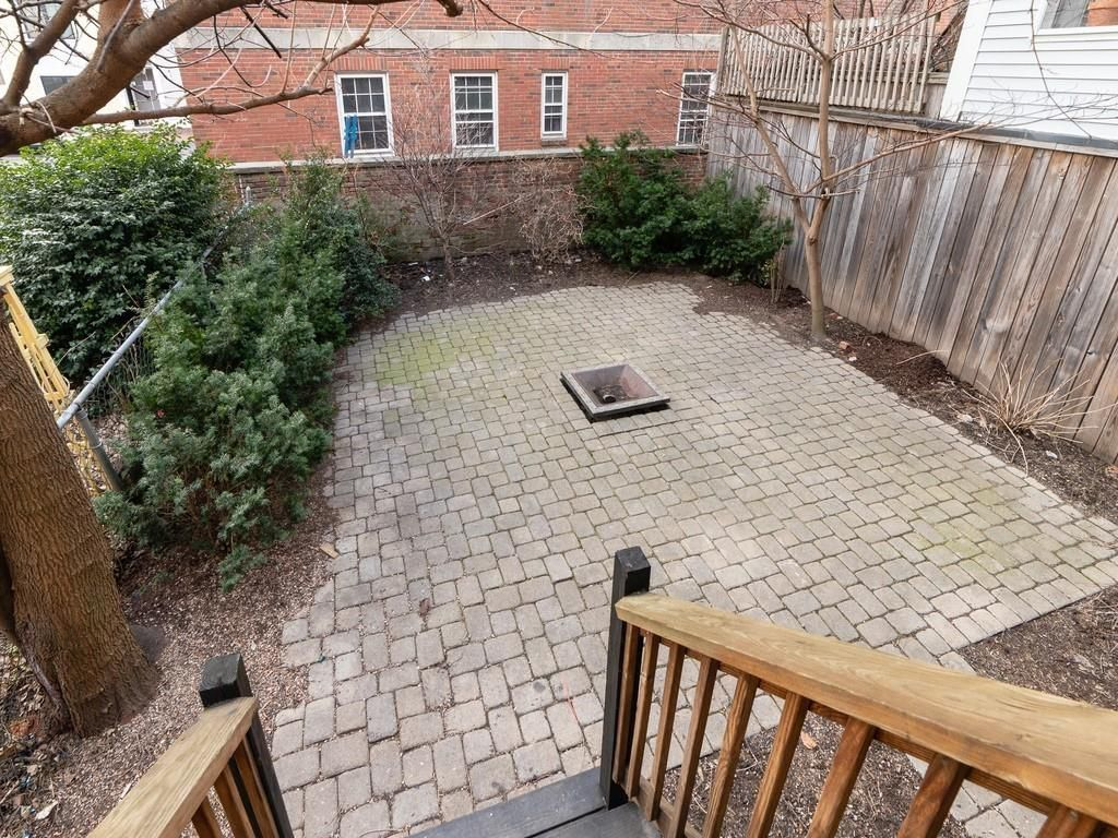 An empty, fenced-in brick patio at the bottom of some wooden stairs.