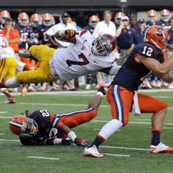 Syracuse quarterback Ryan Nassib, right, avoids a tackle by Southern California safety T.J. McDonald (7) as McDonald goes over Syracuse running back Prince-Tyson Gulley during the second quarter of an NCAA college football game Saturday, Sept. 8, 2012, in East Rutherford, N.J.