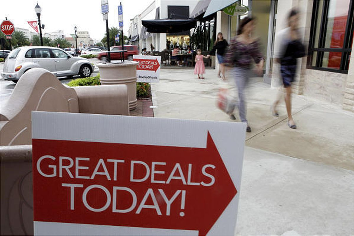 Holiday shoppers walk around the Pembroke Gardens shopping center in Pembroke Pines, Fla., Sunday.