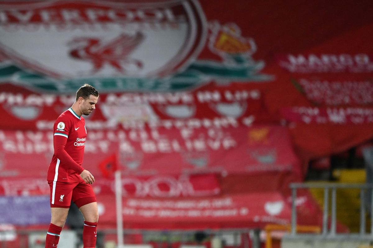 Jordan Henderson of Liverpool leaves the pitch as he is substituted off due to injury during the Premier League match between Liverpool and Everton at Anfield on February 20, 2021. Behind the captain is a banner-laden Kop.