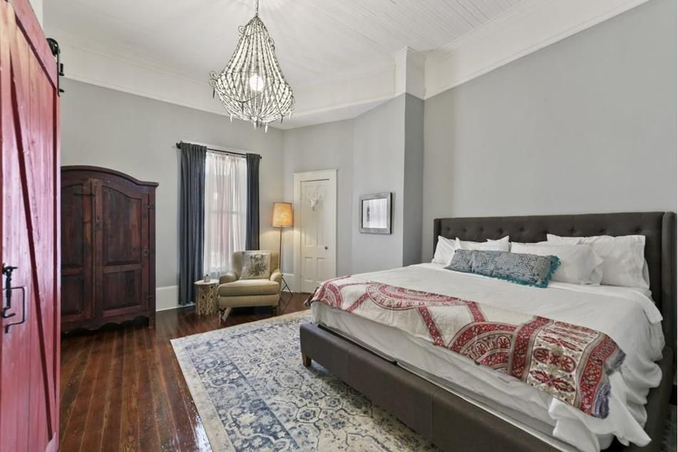 A big grey bedroom with a white bed.