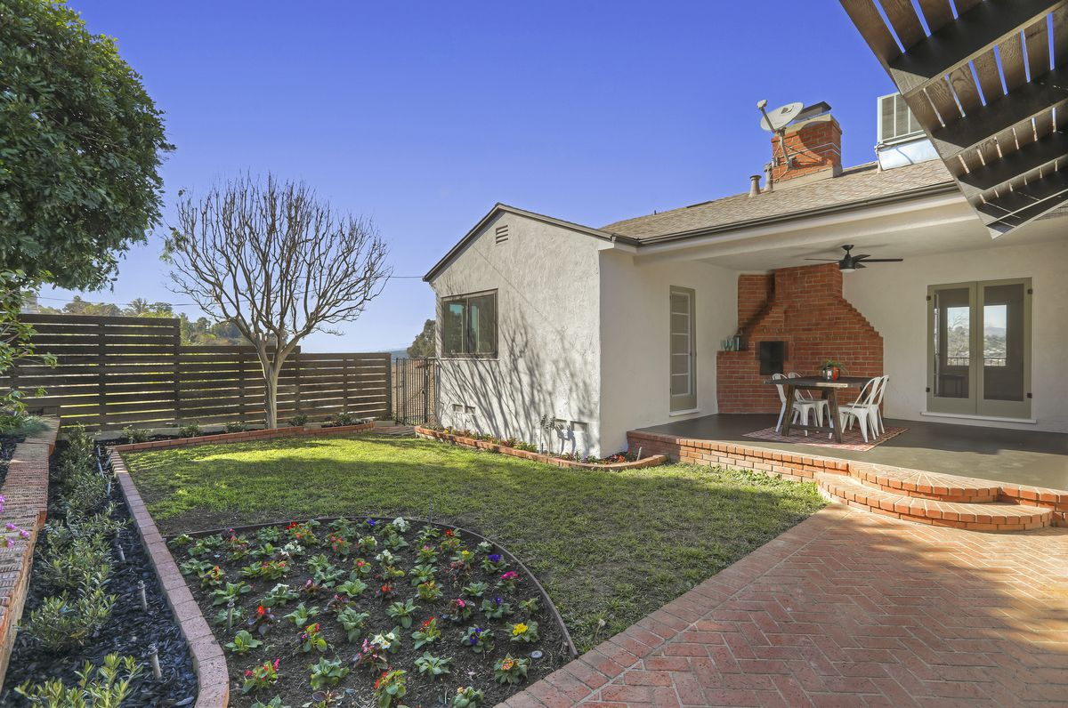A photo of a backyard with a covered patio and a brick fireplace built into the exterior of the house.