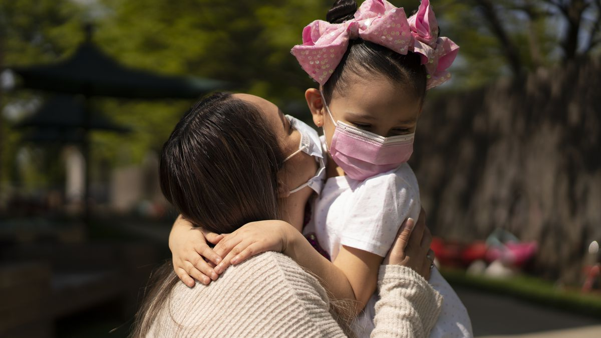 A mother wearing a tan shirt and a protective mask holds her daughter, who is wearing a white shirt, pink mask and pink polka-dot bow. The background is a swirl of green trees.