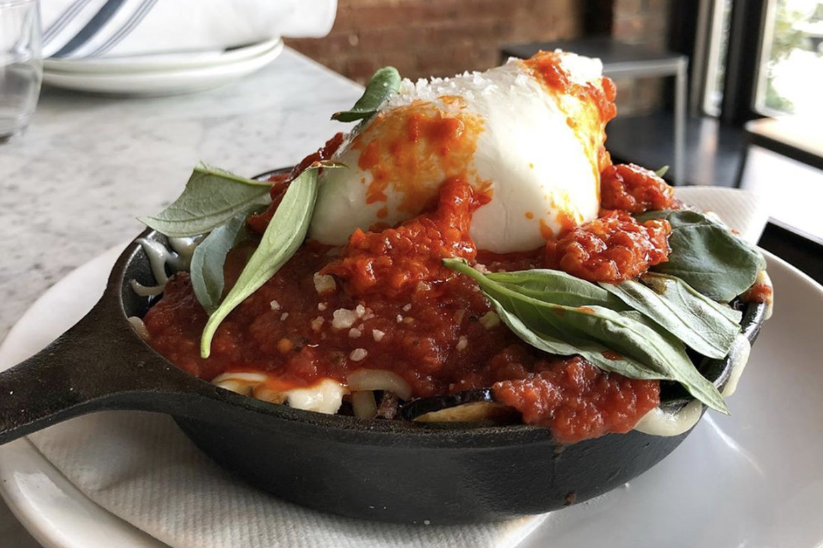 The personal sized black cast iron skillet stuffed with fried eggplant and topped with dollops of chunky red sauce, hunks of burrata, sprinkles of mozzarella, and Calabrian chiles with basil leaves