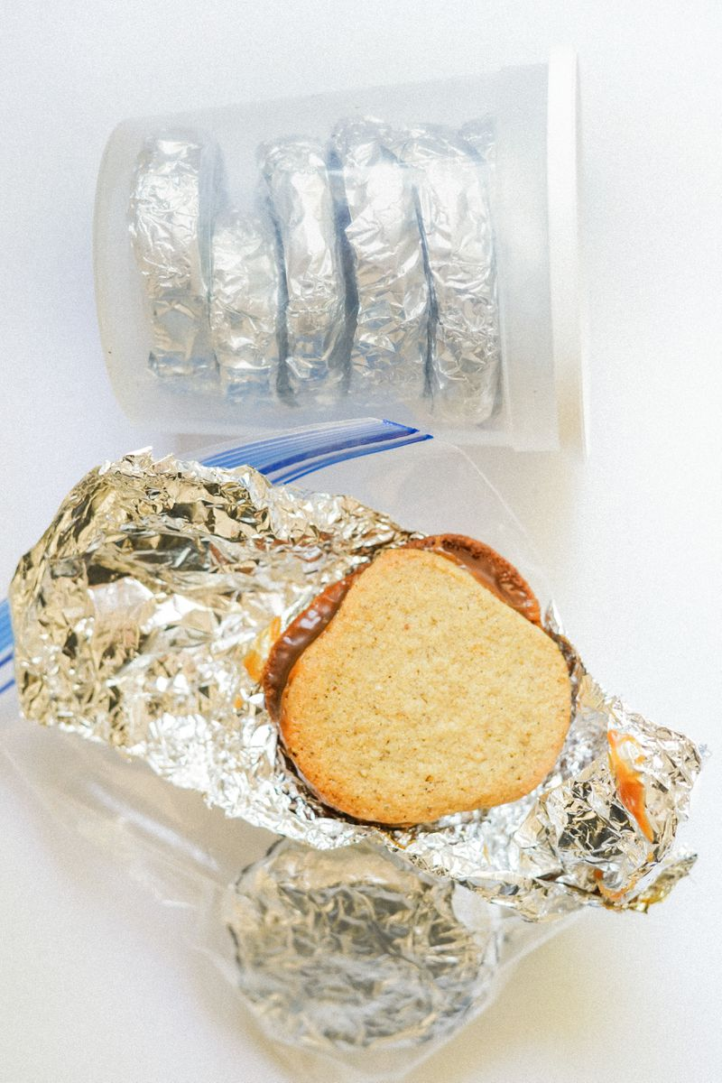 Sandwich cookies with a caramel center, wrapped in tin foil and placed inside a plastic container.
