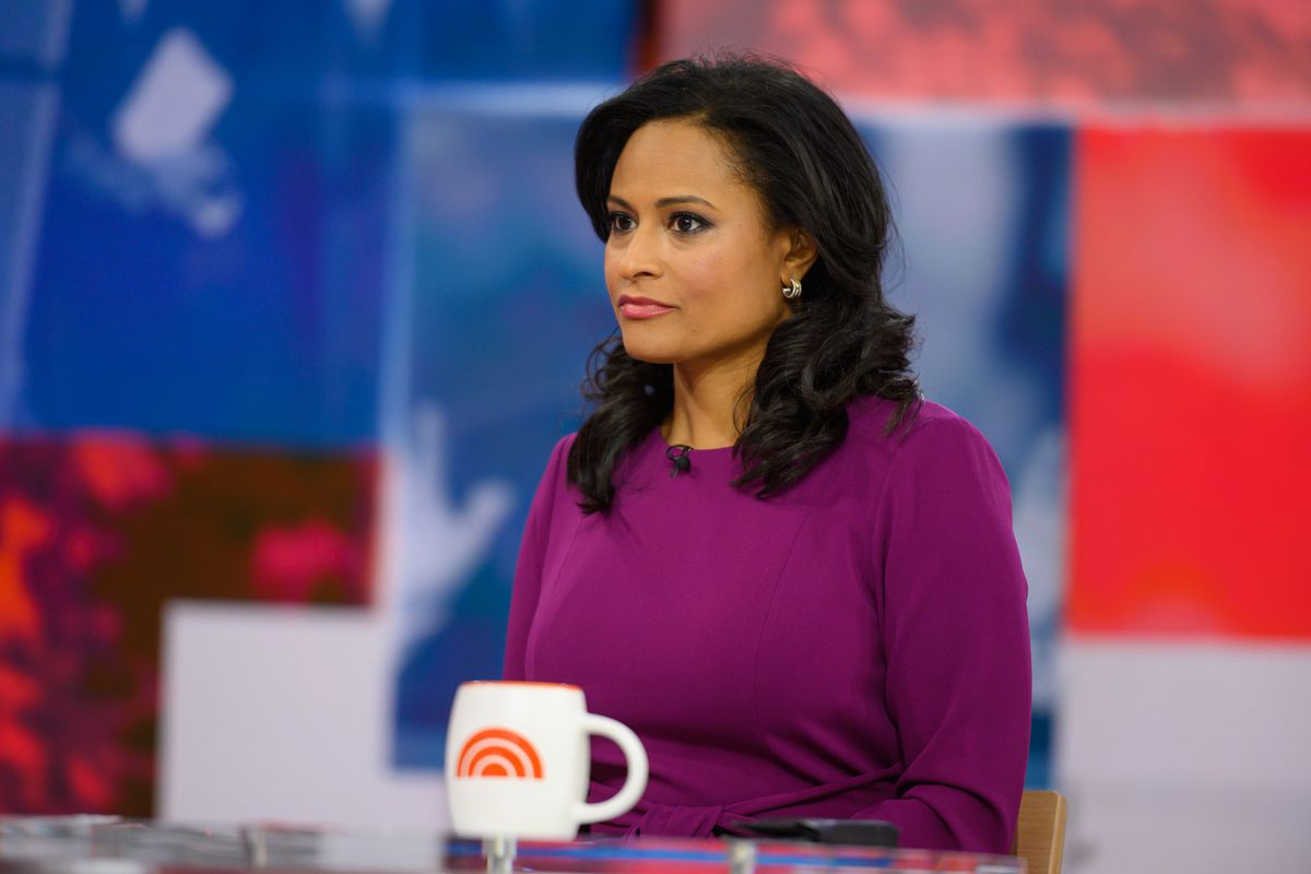 Weekend Today co-anchor Kristen Welker wearing a purple sweater. A white mug bearing the Today logo sits on the table in front of her.