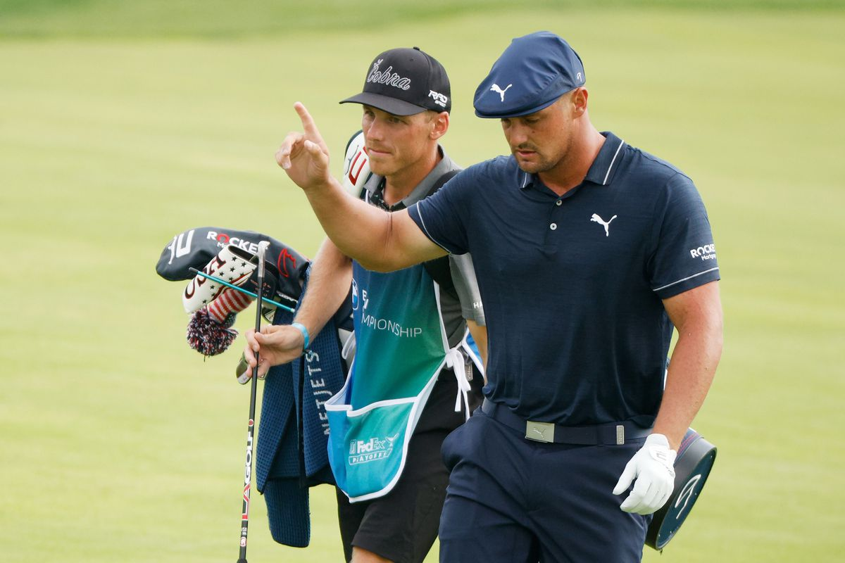 Bryson DeChambeau of the United States reacts as he walks up the 18th fairway with his caddie Brian Zeigler during the second round of the BMW Championship at Caves Valley Golf Club on August 27, 2021 in Owings Mills, Maryland.