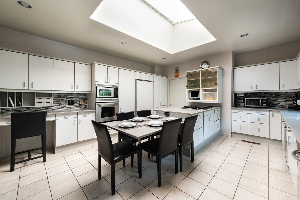 A huge white kitchen with a big skylight overhead.