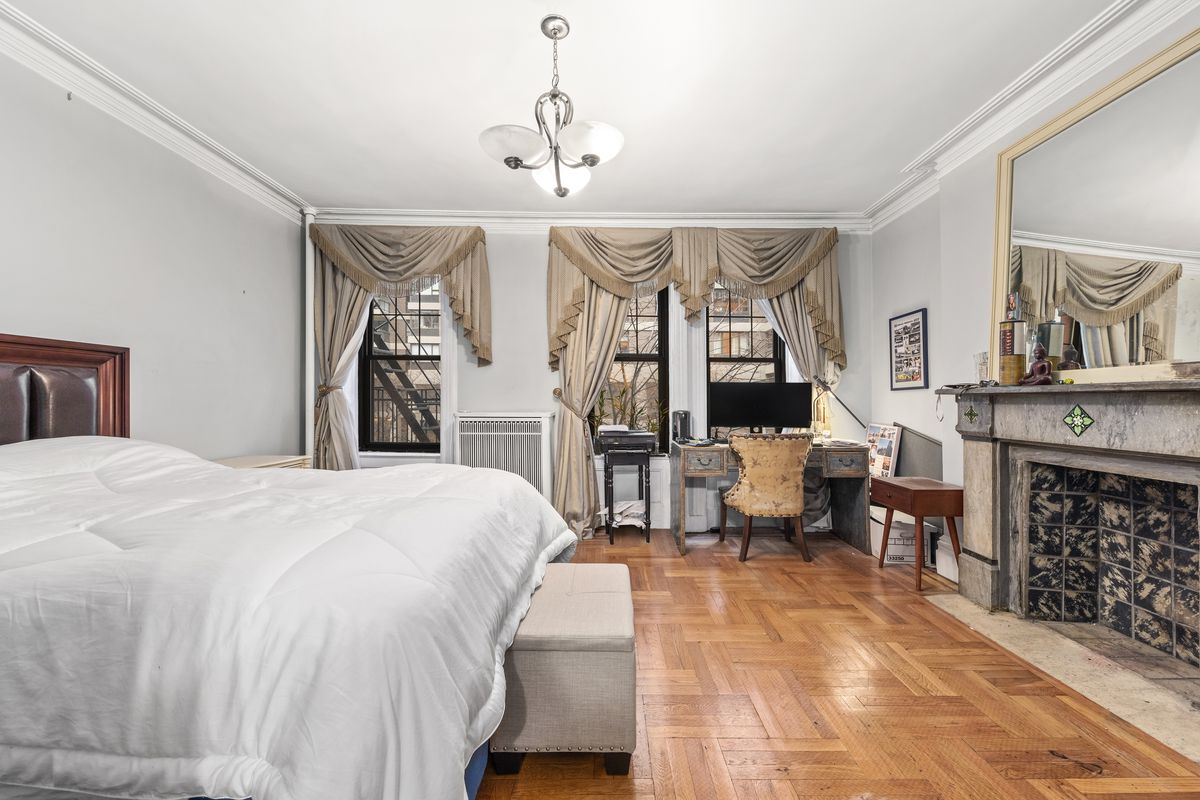 A bedroom with a fireplace, three windows, hardwood floors, and a large bed.