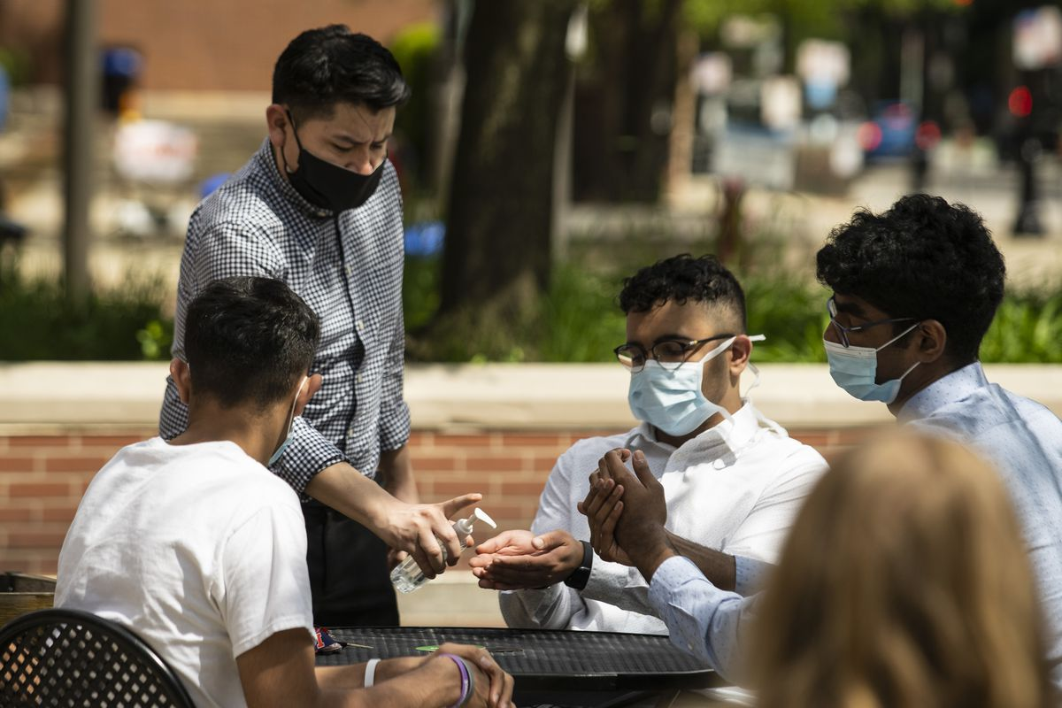 General manager Juan Becerril, 35, of Chicago, dispenses hand sanitizer to customers preparing to eat lunch on the patio at Flat Top Grill in Evanston in May.