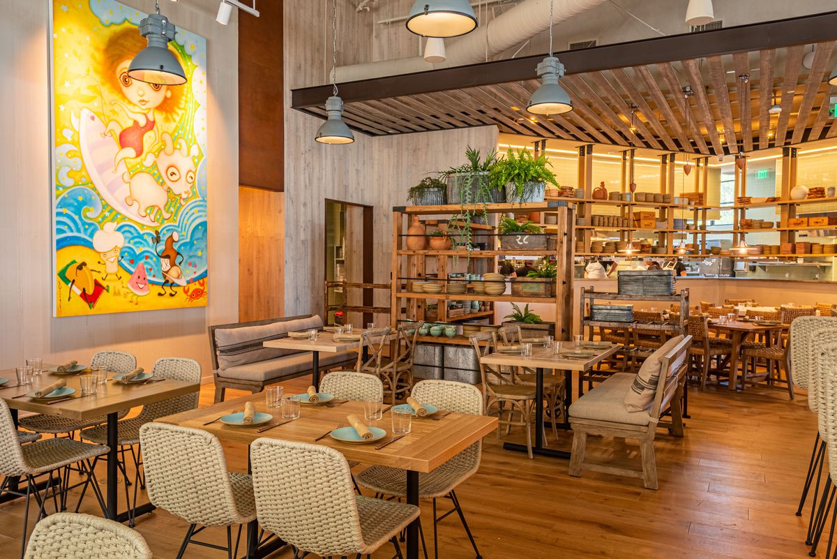 AN open restaurant with art on the walls, lots of warm light, and more.
